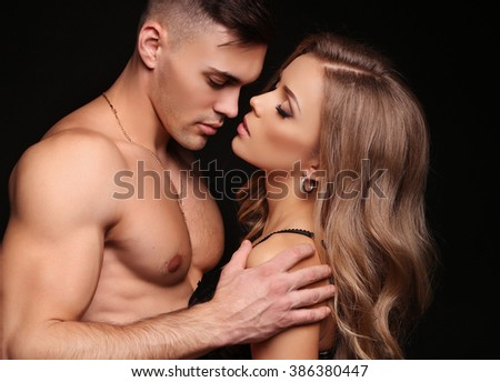fashion studio photo of beautiful couple. gorgeous woman with long blond hair posing with handsome brunette man with sportive muscular torso