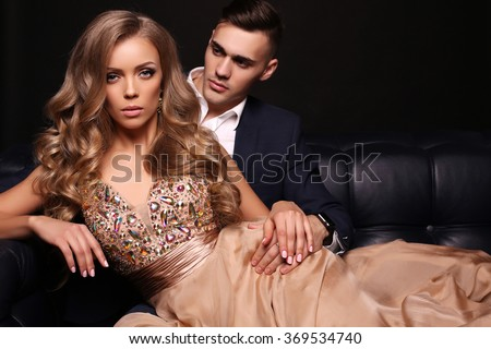 fashion studio photo of beautiful couple in elegant clothes, gorgeous woman with long blond hair posing with handsome brunette man  - stock photo