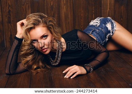 fashion studio photo of beautiful sensual woman with blond curly hair wearing jeans shorts,lying on wood floor - stock photo