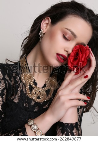 fashion studio photo of beautiful sensual woman with dark hair and bright makeup, holding red rose flower in hands