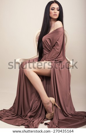 fashion studio photo of beautiful sexy woman with long straight hair wearing elegant dress