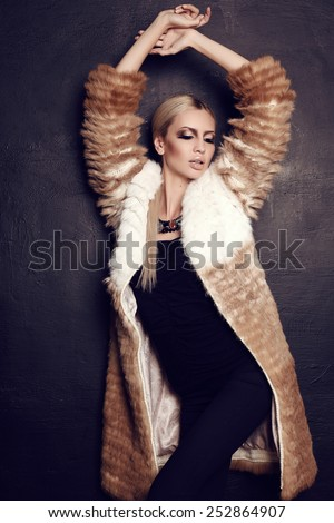 fashion studio photo of beautiful woman with long blond hair with bright makeup and bijou,wearing fur coat