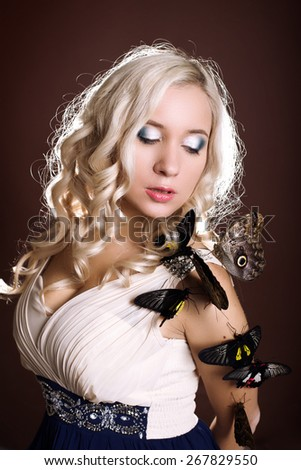 fashion studio photo of beautiful woman with long blonde hair wearing elegant dress,posing with a lot of tropical butterflies - stock photo