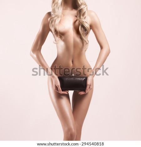 Fashion studio photo of elegant nude woman with clutch - stock photo