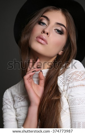 fashion studio photo of gorgeous sensual woman with dark straight hair wears elegant clothes,black hat and bijou