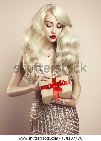 Fashion studio photo of luxury blonde with Christmas gift. Merry Christmas. Happy New Year - stock photo