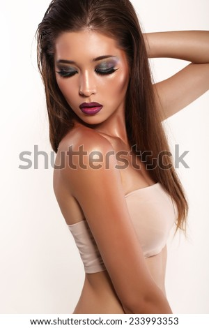 fashion studio photo of sensual beautiful asian look woman with long dark hair and bright makeup