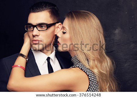 fashion studio photo of sexy impassioned couple. handsome businesslike man in glasses posing with  beautiful girl with blond hair