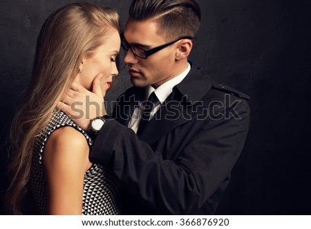 fashion studio photo of sexy impassioned couple. handsome businesslike man in glasses with beautiful girl with long blond hair  - stock photo