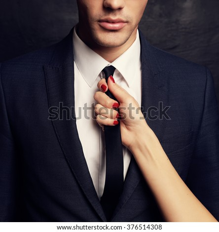 fashion studio photo of sexy impassioned couple. handsome businesslike man in glasses,woman's hand holding his tie  - stock photo