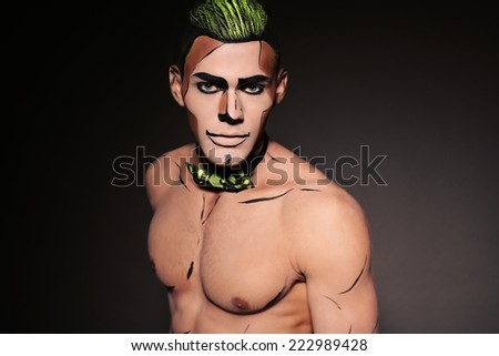fashion studio photo of sexy man with naked chest and bright extravagant make up for Halloween party