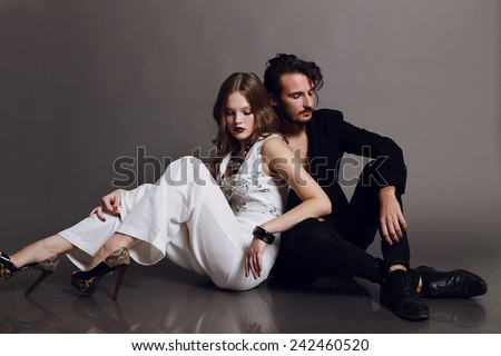 Fashion studio photo of sexy young coupl of brown-haired woman and brunette man dressed in black and white suits like yin-yang and sitting on the flor,love,lovers,Valentines day - stock photo