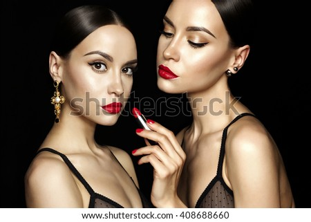 Fashion studio photo of two beautiful young ladys with red lipstick. Perfect face makeup. Beauty and jewelry - stock photo