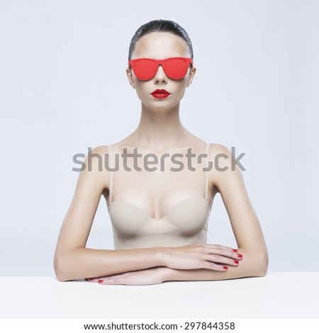 Fashion studio photo of young elegant lady in red sunglasses - stock photo