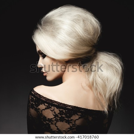 Fashion studio portrait of beautiful blonde woman with elegant hairstyle on black background