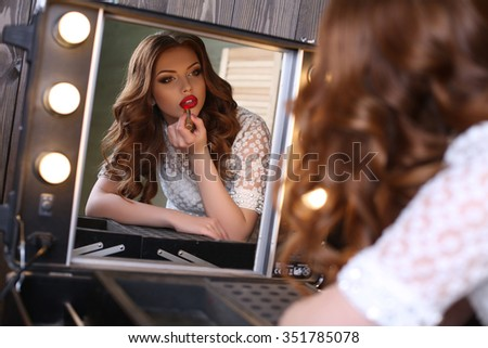 fashion studio portrait of beautiful glamour girl with dark curly hair making makeup, paints her lips, looking at mirror