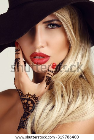 fashion studio portrait of beautiful sensual woman with blond hair with evening makeup and henna tattoo on hands