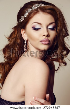 fashion studio portrait of beautiful sensual woman with dark  hair and bright makeup, with bijou  and hair accessory