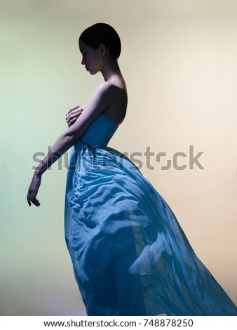Fashion studio portrait of beautiful woman in azure flowing dress on colorful background. Asian beauty.