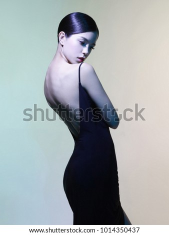 Fashion studio portrait of beautiful woman in black dress on colorful background. Asian beauty.