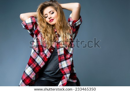 Fashion studio portrait of beautiful woman with amazing hairs and beautiful face, wearing bright smoky rock make up, and big relaxed grunge plaid shirt. Posing alone, grey background. - stock photo