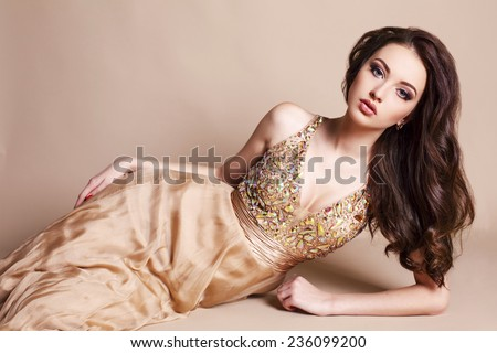 fashion studio portrait of beautiful young girl with dark hair wearing luxurious beige dress - stock photo