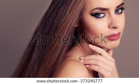 fashion studio portrait of beautiful young woman with blond straight hair and evening makeup