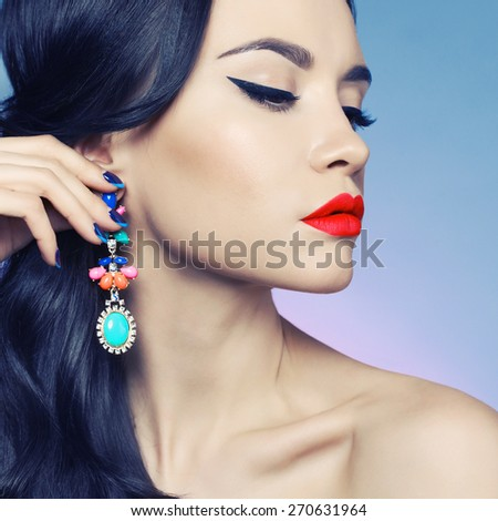 Fashion studio portrait of beautiful young woman with earring. Beauty and makeup. Jewelry and accessories - stock photo
