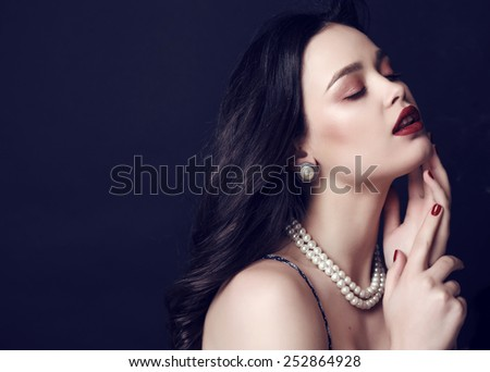 fashion studio portrait of gorgeous beautiful woman with dark hair and bright makeup with pearls necklace - stock photo