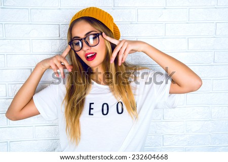 Fashion studio portrait of pretty young hipster blonde woman with bright sexy make up and glasses , wearing stylish urban t shirt and hat, White urban wall background.  - stock photo