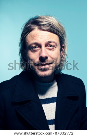 Fashion studio portrait of smiling young man with long blond hair wearing sweater and black jacket. Blue background.