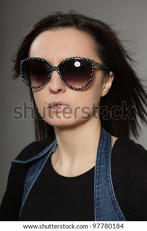 Fashion studio portrait of stylish young pretty woman with brown long hair isolated on grey background.