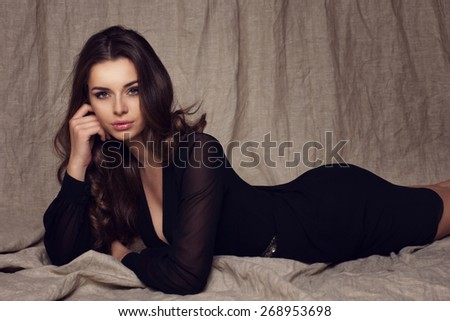 Fashion studio portrait of young beautiful female model lying in black sexy dress on textile background. Glamour photo of pretty girl with slim figure. - stock photo