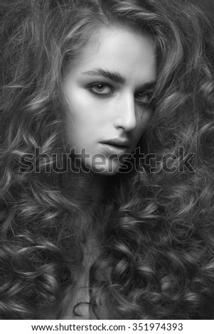 Fashion studio portrait of young beautiful woman with curly hairstyle