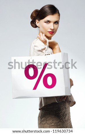 Fashion studio shot of beautiful woman with a luxurious and healthy hair with shopping bag. Professional makeup and hairstyle