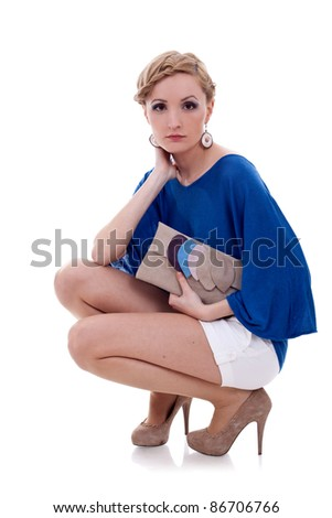 Fashion studio shot of beautiful woman with brown purse, on white background - stock photo