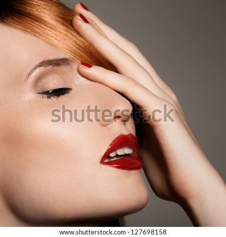 Fashion studio shot of beautiful young woman with make-up. Close-up portrait. - stock photo