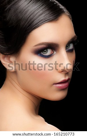 Fashion studio shot of young beautiful woman with bright violet makeup and wet hairstyle