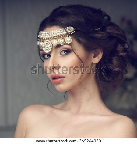 Fashion style beauty portrait of young pretty girl with perfect makeup and hairstyle looking at you or in the camera