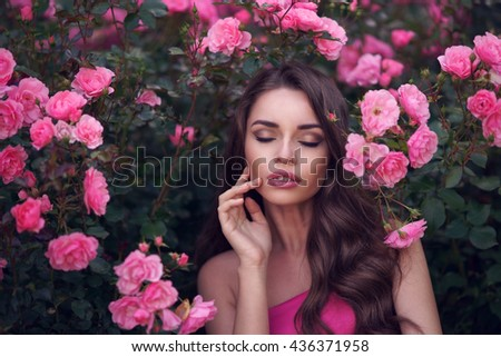 Fashion style beauty romantic portrait of young pretty beautiful woman with long curly hair posing between pink roses. Stunning girl with closed eyes - stock photo