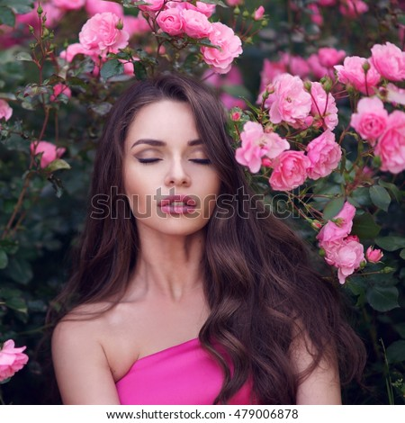 Fashion style beauty romantic portrait of young pretty beautiful woman with long curly hair posing between pink roses. Stunning girl with closed eyes