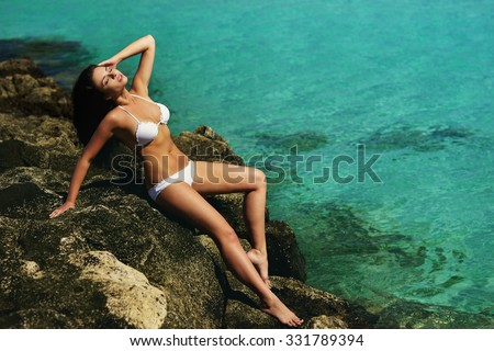 Fashion style full length portrait of young beautiful sexy tanned girl in white bikini sitting at rocks near blue green clear ocean sea water. Sunbathing woman. Vogue style - stock photo