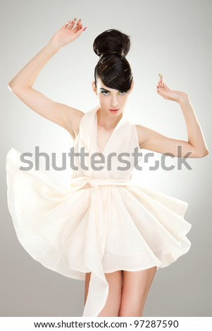 Fashion style - luxurious young woman in light flying dress posing in studio. - stock photo