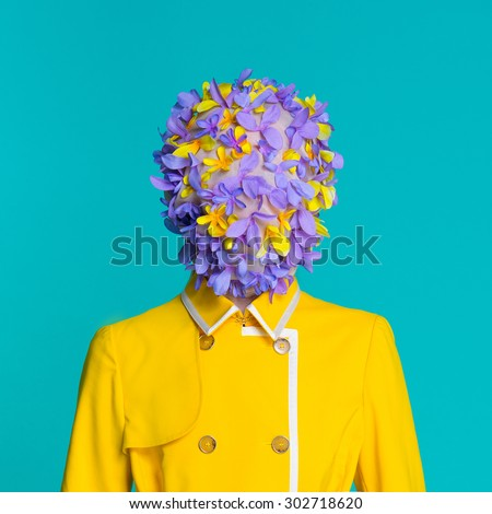 Fashion style model in yellow coat and art accessories  on head posing in the studio on blue background - stock photo