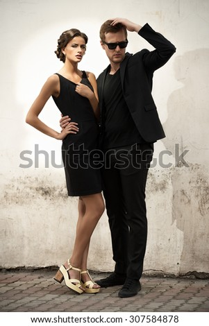 Fashion style photo of a beautiful couple over city background.  - stock photo