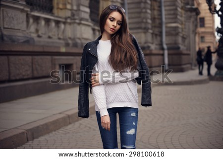 Fashion style portrait of young beautiful calm female model posing at city street with magnificent architecture. Full body portrait.