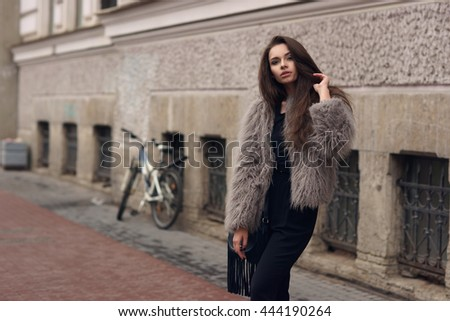 Fashion style portrait of young beautiful elegant woman in black dress and gray fur coat walking at city street - stock photo