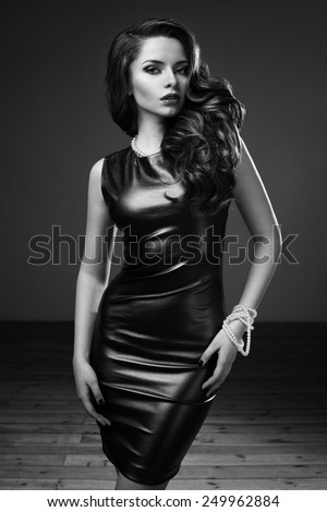 Fashion style portrait of young beautiful lady with dark curly hair posing in sexy short green dress. Portrait in black and white colors - stock photo