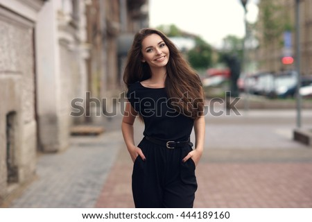 Fashion style portrait of young happy smiling beautiful elegant woman in black dress walking at city streets.
