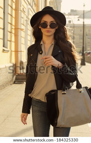 fashion style portrait of young trendy girl walking along the street - stock photo